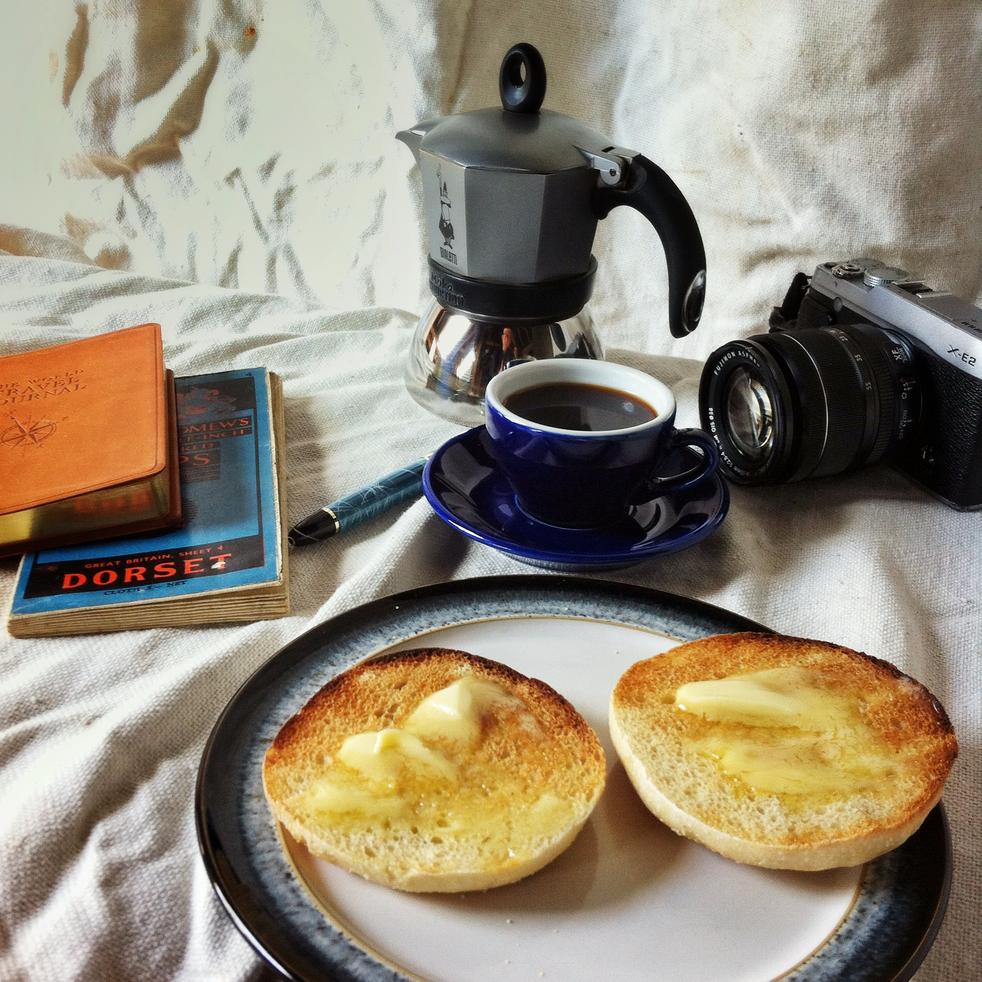 Travel photo of a toasted muffin with camera coffee and map